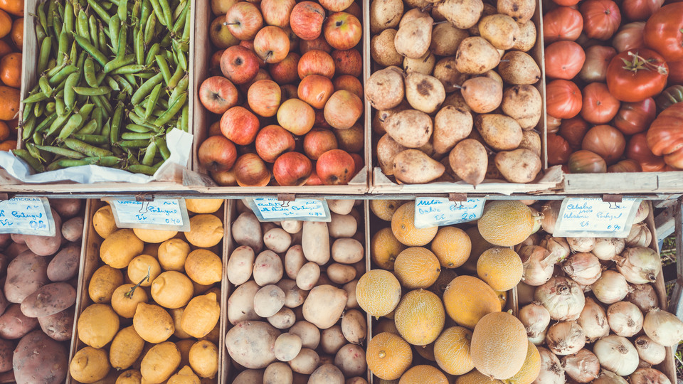 Boxes with fruit, vegetables and pototes photographed from above.