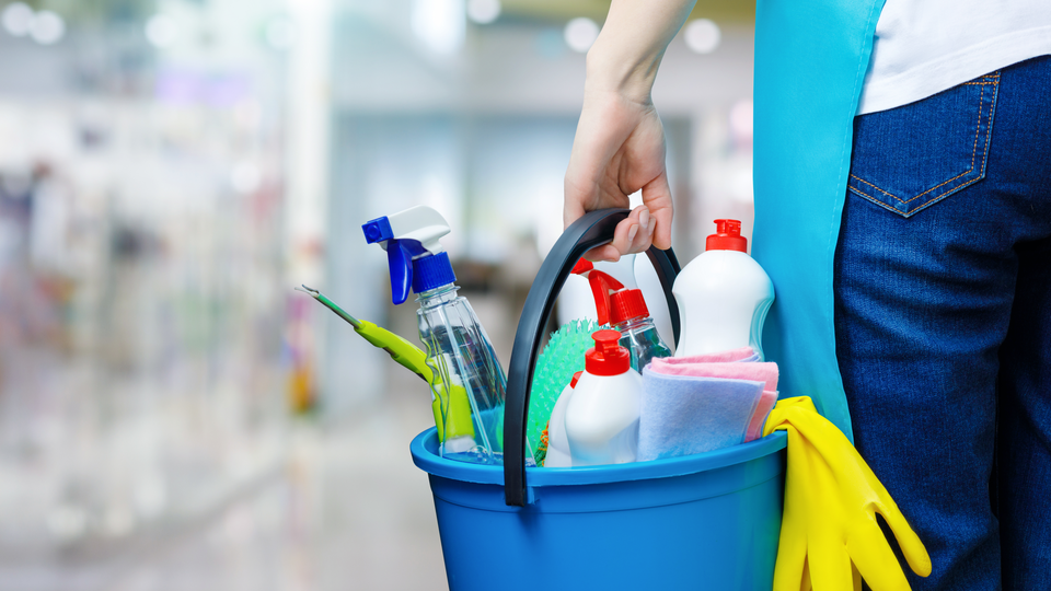 A cleaning woman is standing inside a building holding a blue bucket filled with chemicals and facilities for tidying up in her hand.